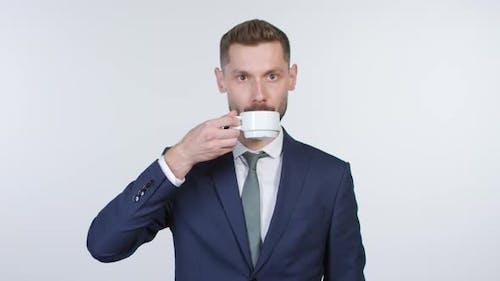 Emotionless Geschäftsmann trinken Kaffee