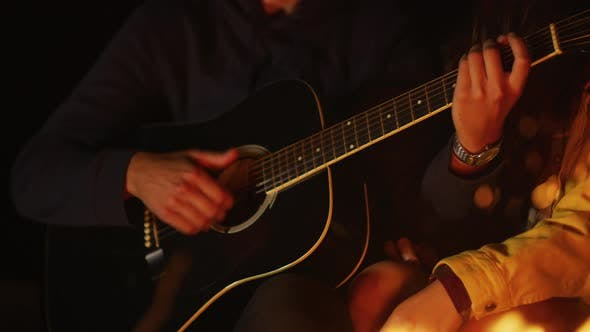 Thumbnail for Playing guitar near a campfire