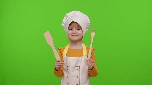 Child Girl Kid Dressed As Cook Chef Showing Wooden Fork and Spatula Smiling Nods Head in Agreement
