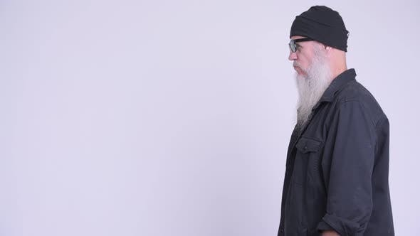 Profile View of Mature Bearded Hipster Man Removing Sunglasses and Looking at Camera