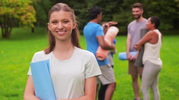 Smiling Woman with Yoga Mat Over Group of People
