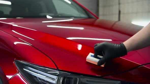 Thumbnail for Auto-Detaillierung - Man wendet Nano-Schutzbeschichtung oder Wachs auf rotes Auto an. Abdeckung der Motorhaube mit einem
