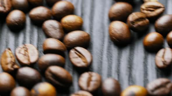 Thumbnail for Coffee grain. Brown roasted coffee beans scattered on wooden surface.