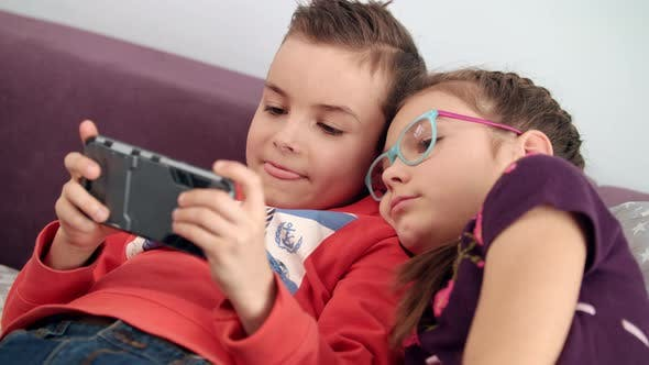 Thumbnail for Kids Using Mobile Phone at Home. Sister Looking Into Smartphone in Boy Hands