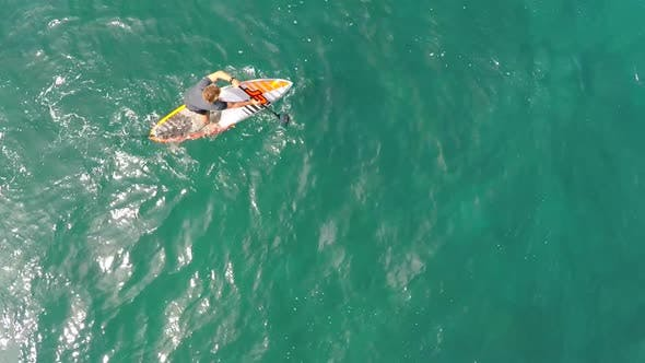 Aerial view of a man sup stand-up paddleboard surfing in Hawaii