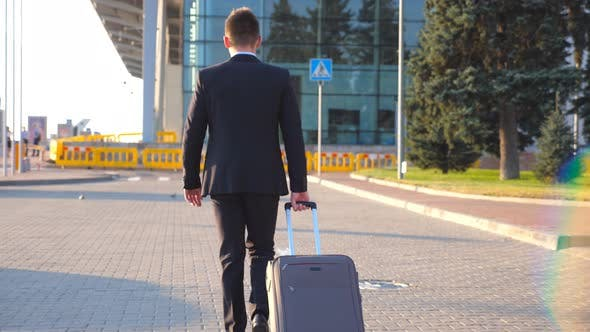 Thumbnail for Rear View of Unrecognizable Young Businessman Walking To Airport Terminal and Pulling Suitcase