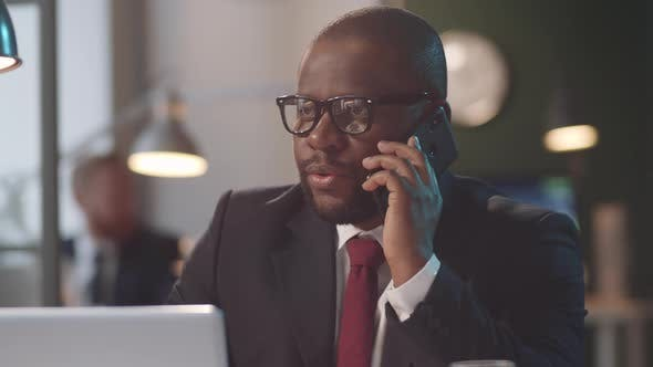 Afro-American Businessman Talking on Phone in Office