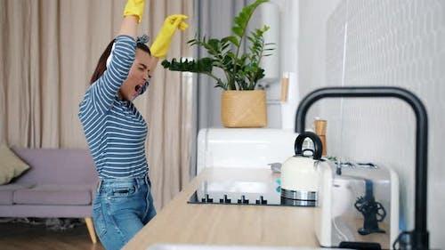 Joyful Lady Cleaning Kitchen Then Dancing Singing Enjoying Music in Headphones
