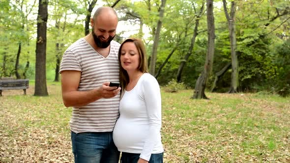 Thumbnail for Handsome Man and Pregnant Woman Work Together on Smartphone in Park