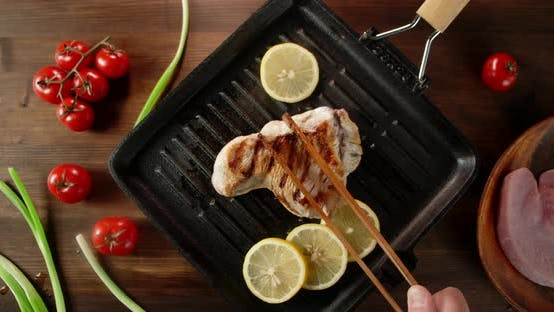 Turkey Fillets Are Fried in Pan with Pieces of Lemon