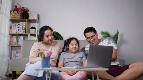 Junge Eltern, die kleine Tochter unterrichten, benutzen Laptop