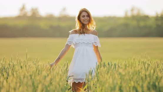 Happy Young Woman Whirls and Jumps in the Field