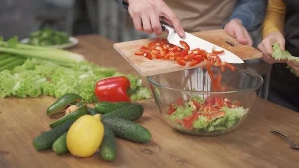 Nahaufnahme von Männerhänden, die Gemüse auf Holzschneidebrett für Salat auf dem Tisch schneiden
