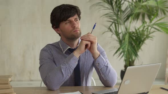 Thoughtful Serious Brunette Man Sit with Laptop Thinking of Project