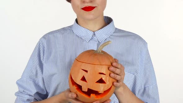 Thumbnail for Woman Wearing Red Lipstick Holding Up Carved Halloween Pumpkin