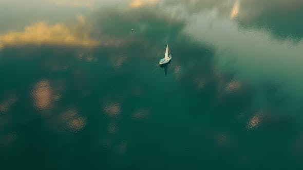 Thumbnail for One Yacht in the Sea From a Bird's Eye View at Sunset. The Sky Is Reflected in the Water. Flight