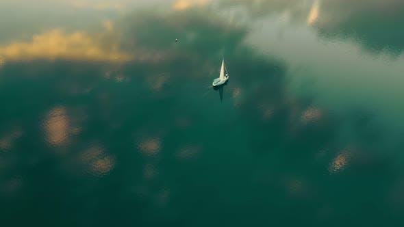 Eine Yacht im Meer aus der Vogelperspektive bei Sonnenuntergang. Der Himmel spiegelt sich im Wasser wider.  Flug