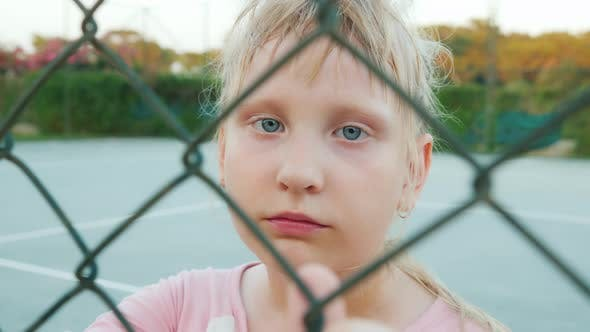 Cover Image for Tired Child Looking Through the Fence Mesh