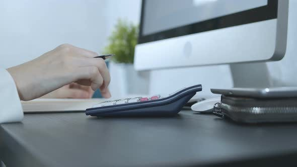 Thumbnail for Accountant Working With Calculator And Writing