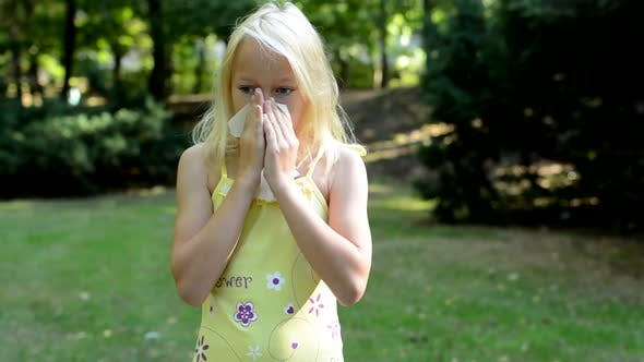 Thumbnail for Little Cute Girl Blows Her Nose in the Park - She Has an Allergy
