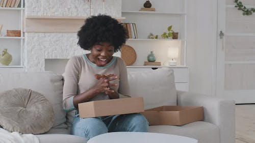 Excited Mixed Race Young Woman Customer Opening Parcel Box at Home