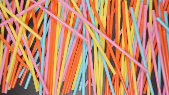 Many colour tubes fall on a black table