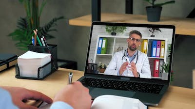 Man Doctor in Laptop Screen Tells Consults Online Video Call Computer Webcam