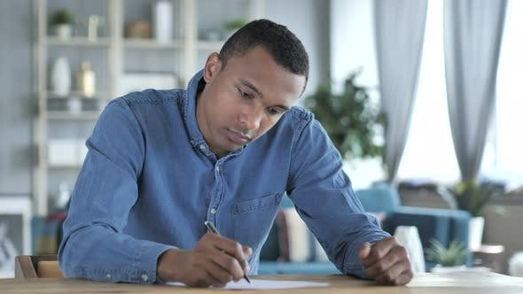 Thumbnail for Young African Man Writing on Documents in Office, Paperwork