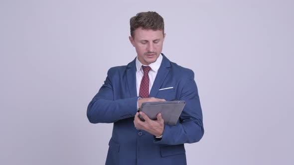 Thumbnail for Handsome Bearded Businessman Talking on the Phone and Using Digital Tablet