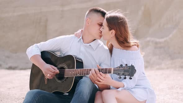 Man Holding Guitar and Woman Kissing in Career in Summer
