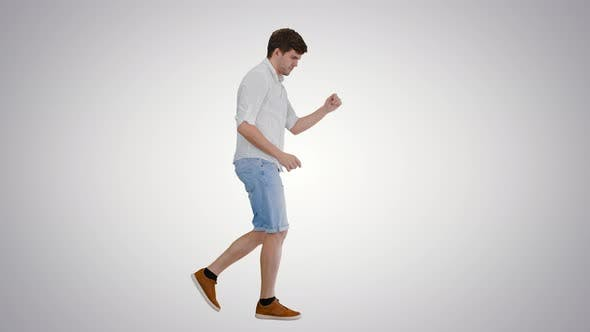 Young Man in Casual Clothes Dancing Happily While Walking on Gradient Background.