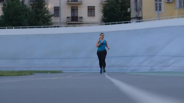 Thumbnail for Overweight Woman Runner Training on Stadium Track