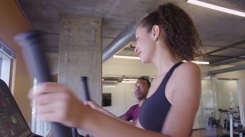 Hispanische Frau lächelnd und chatten mit schwarzem Freund, während mit elliptischen Fitness-Maschine