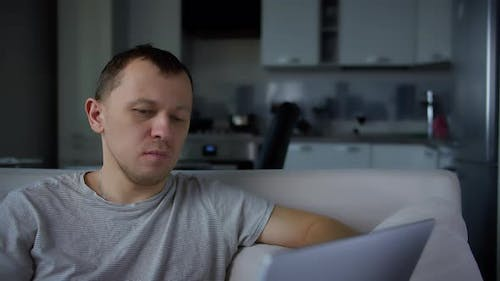 A man sitting comfortably on the sofa in the evening against the background of the kitchen