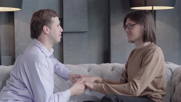 Thumbnail for Seitenansicht von Homosexuell Paar sitzen auf Couch und sprechende Hand halten. Porträt selbstbewusster Junge