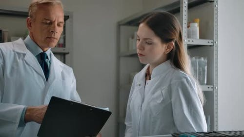 Middle Shot of Two Pharmacists Talking About Medicine Indoor of Drug Store