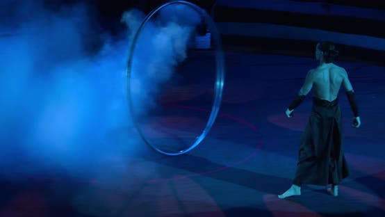 Thumbnail for Circus Show in Dark Lighting and Smoke Wheel Gymnastics By a Young Man