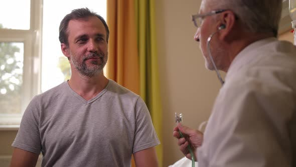 Thumbnail for Aging Doctor Listening To Patient with Stethoscope