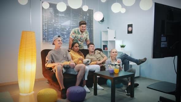 Thumbnail for Junge Leute sehen fern und essen zusammen Snacks zu Hause