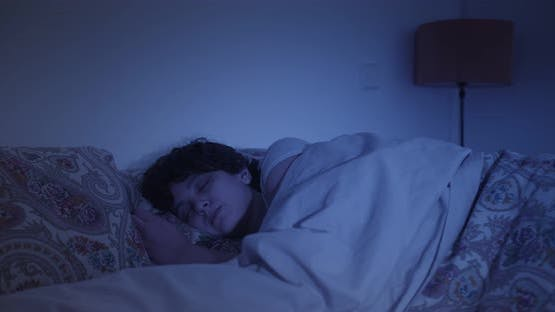 Young woman sleeping at home in bed