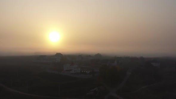 The Bright Sun Shines Over a Small Town on an Autumn Morning. Morning Foggy Sky. Lightly Drizzle