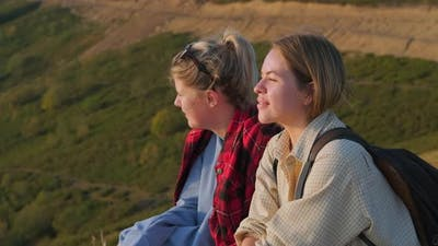Charming Teen Girls Friends are Relaxing on Slope of Mount at Summer