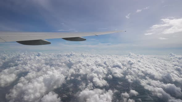Thumbnail for The Plane Flies High Above the Clouds and Ground. The Wing of Aircraft in Blue Sky at the Horizon