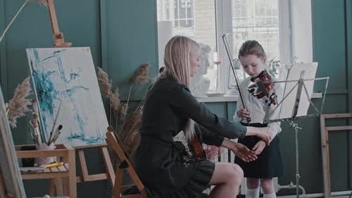 Violin Teacher Puts the Hand of Her Student on the Fretboard