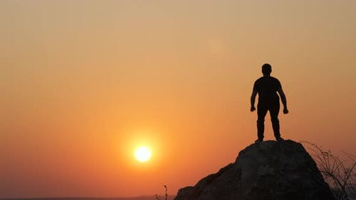 Silhouette of a man hiker jumping alone on big stone at sunset in mountains. Male tourist raising