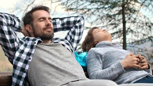 Dad and his teenage son with closed eyes relaxing outdoors