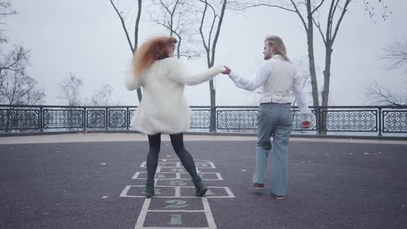 Thumbnail for Young Caucasian Man in Elegant Clothes Holding His Girlfriend's Hand As She Jumping on the Hopscotch