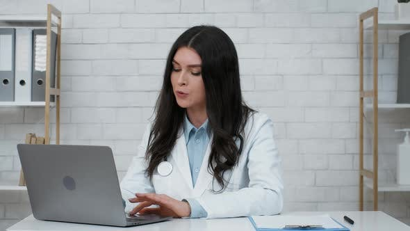 Female Doctor At Laptop Consulting Patient Online Sitting In Clinic