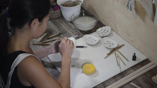 Woman works with earthenware in studio