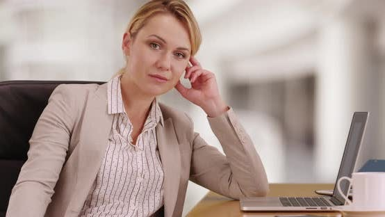 Thumbnail for Businesswoman sitting at desk looking at camera